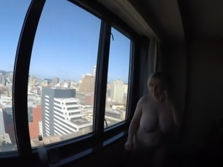 Busty GILF naked overlooking city