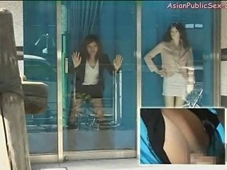 Asian girl is ficled in a store window by a guy behind the curtain.